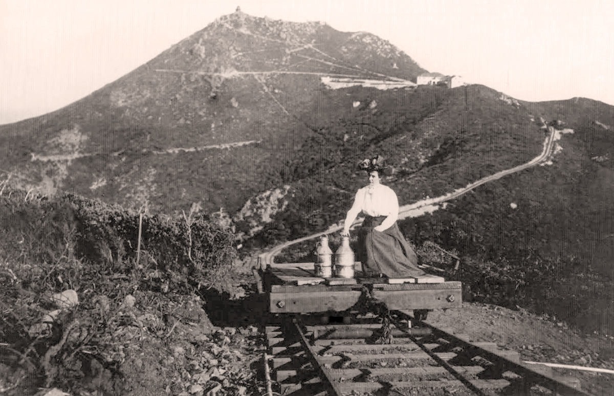 Woman with milk cans on the West Peak radio Station Incline
